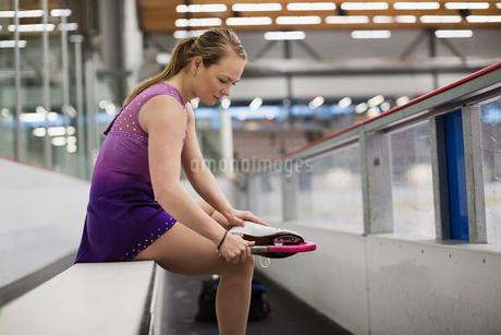 Female figure skater preparing for routine in skating rinkの写真素材 [FYI02300606]