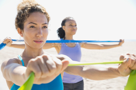 Women exercising with resistance band on beachの写真素材 [FYI02300649]