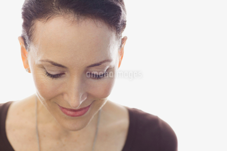 Close-up of woman looking down against white backgroundの写真素材 [FYI02300656]