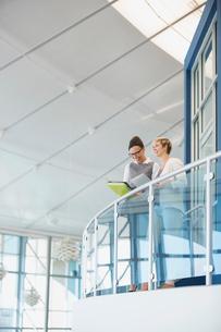 Businesswomen talking on atrium balconyの写真素材 [FYI02300842]