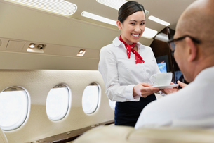 Flight attendant serving coffee to businessman in private jetの写真素材 [FYI02300881]