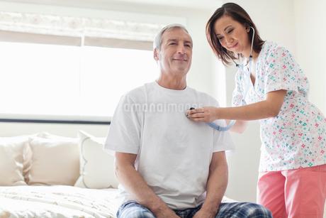Female nurse examining senior man with stethoscope at homeの写真素材 [FYI02301112]