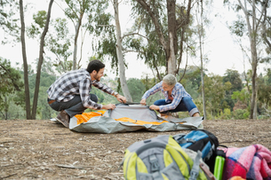 Couple setting up tent in forest with backpacks in foregroundの写真素材 [FYI02301140]