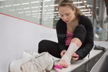 Female figure skater bandaging ankle in skating rinkの写真素材 [FYI02301213]