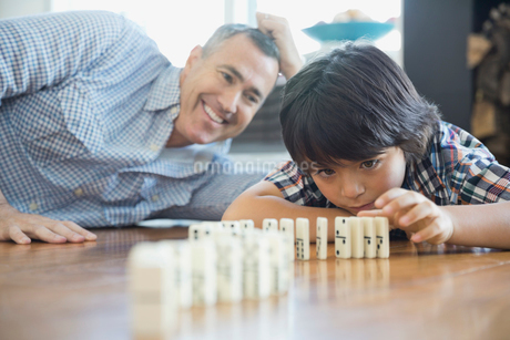 Son and father playing with dominoes at homeの写真素材 [FYI02301230]