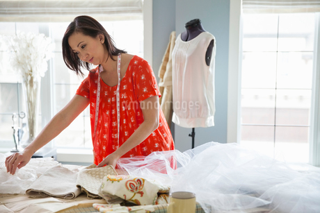 Female seamstress working in home studioの写真素材 [FYI02301344]
