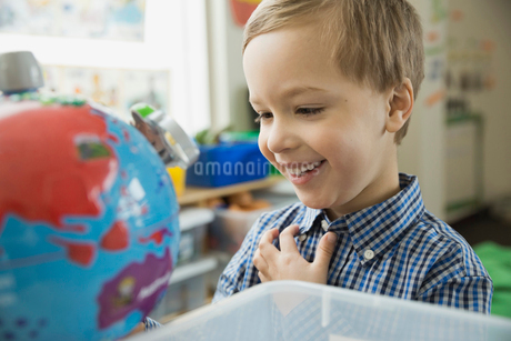Smiling boy looking at globe in schoolの写真素材 [FYI02301391]