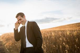 Smiling businessman using smart phone in fieldの写真素材 [FYI02301408]