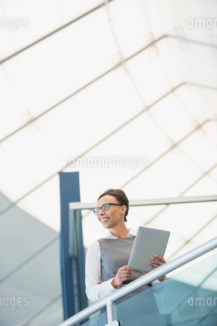 Businesswoman with digital tablet on staircaseの写真素材 [FYI02301420]