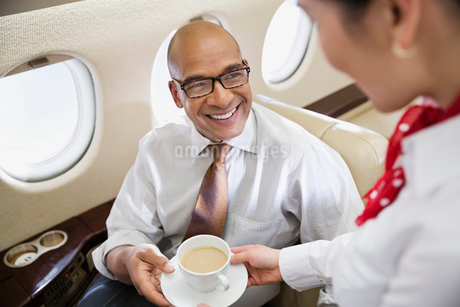 Flight attendant serving coffee to businessman in private jetの写真素材 [FYI02301487]