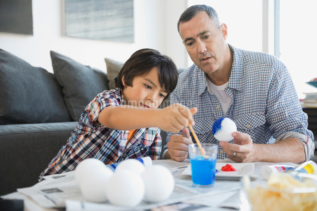 Father and son painting solar system model at homeの写真素材 [FYI02301527]