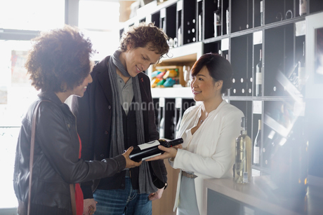Sommelier recommending bottle to couple in wine storeの写真素材 [FYI02301528]