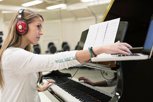 Female student listening to music on laptop in college music roomの写真素材 [FYI02301556]