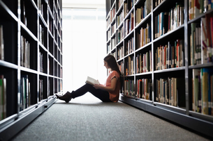 Female student sitting on library floor at college campusの写真素材 [FYI02301588]