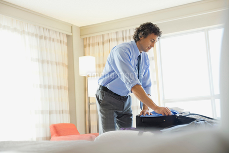 Businessman packing suitcase in hotel roomの写真素材 [FYI02301616]