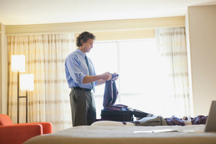 Businessman packing suitcase in hotel roomの写真素材 [FYI02301649]