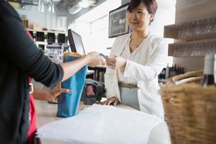 Cashier taking customer credit card in wine storeの写真素材 [FYI02301650]