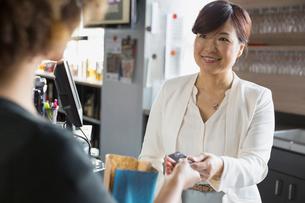 Cashier taking customer credit card in wine storeの写真素材 [FYI02301692]