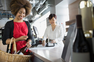 Woman purchasing wine in storeの写真素材 [FYI02301721]