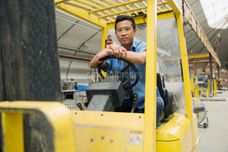 Portrait of worker operating forklift in factoryの写真素材 [FYI02301742]