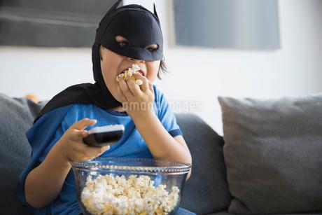 Boy dressed in superhero costume watching TV at homeの写真素材 [FYI02301768]