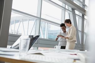 Businesswomen using digital tablet in office buildingの写真素材 [FYI02301772]