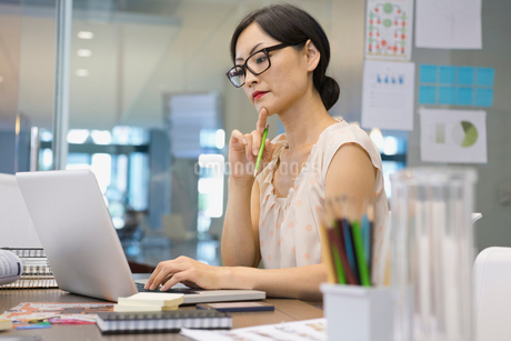 Businesswoman working on laptop at office deskの写真素材 [FYI02301871]