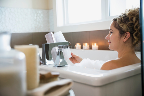 Mature woman reading book in bathtubの写真素材 [FYI02301904]