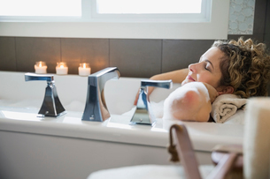 Mature woman with eyes closed relaxing in bathtubの写真素材 [FYI02302080]