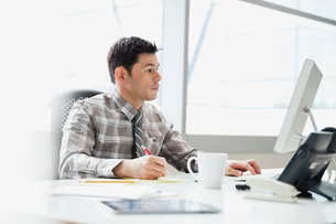 Businessman working at desk in officeの写真素材 [FYI02302151]