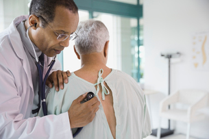Male doctor checking senior patient with stethoscopeの写真素材 [FYI02302233]