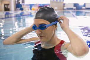 Woman putting on goggles in swimming poolの写真素材 [FYI02302291]