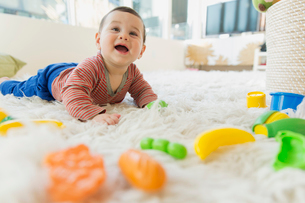Baby lying on fuzzy rug with plastic toys.の写真素材 [FYI02302371]