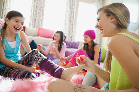 Cheerful girls painting toenails at slumber partyの写真素材 [FYI02302378]