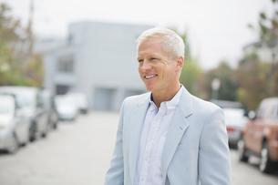 Smiling man looking away outdoorsの写真素材 [FYI02302563]