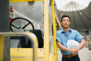 Confident worker leaning on forklift in factoryの写真素材 [FYI02302580]