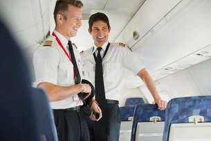 Smiling male pilot and co-pilot standing in airplane cabinの写真素材 [FYI02302653]