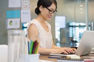 Businesswoman using laptop in officeの写真素材 [FYI02302656]