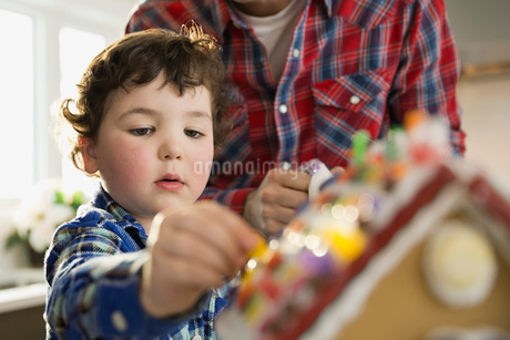 Cute boy decorating gingerbread house during Christmasの写真素材 [FYI02302693]