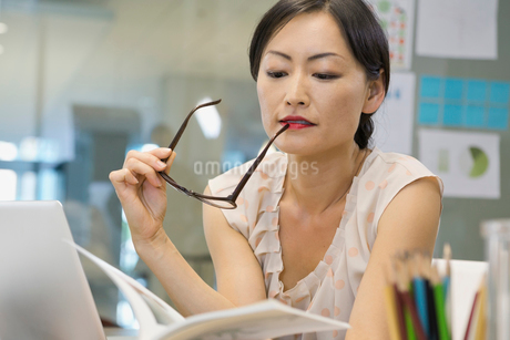 Businesswoman reading book in officeの写真素材 [FYI02302855]