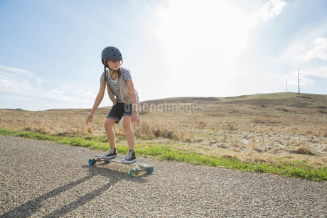 Little girl skateboarding on roadの写真素材 [FYI02302905]