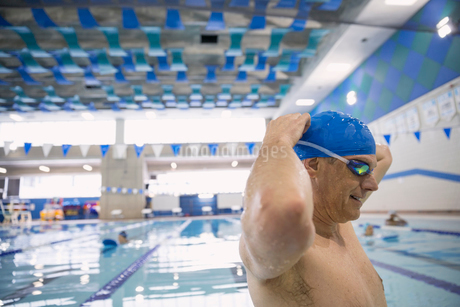 Man putting on goggles at indoor swimming poolの写真素材 [FYI02302922]