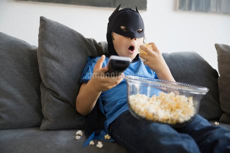 Boy in superhero costume watching TV at homeの写真素材 [FYI02302987]