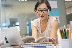 Businesswoman reading book at office deskの写真素材 [FYI02303007]