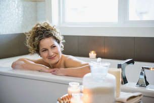 Mature woman looking away while relaxing in bathtubの写真素材 [FYI02303014]