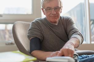 Senior man testing blood pressure at home.の写真素材 [FYI02303149]