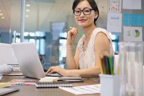 Portrait of confident businesswoman sitting at deskの写真素材 [FYI02303272]
