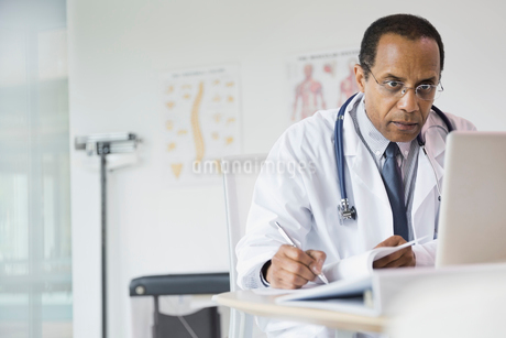 Male doctor taking notes in officeの写真素材 [FYI02303304]