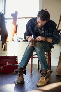 Young man stitching leather wallet in workshopの写真素材 [FYI02303328]