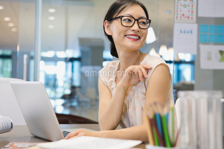 Businesswoman looking away at office deskの写真素材 [FYI02303340]
